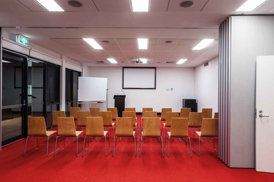 A conference room room with twenty chairs, a whiteboard, a podium and audio visuals