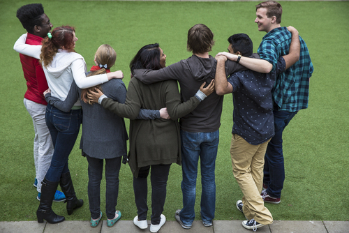 A diverse group of seven students hug each other on a grass