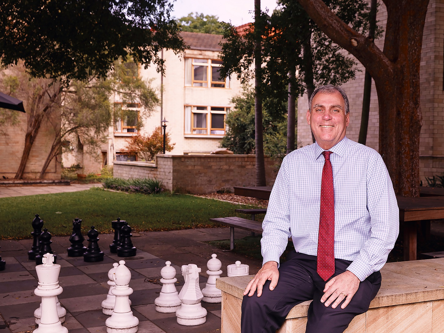 A man (Robert Menzies College Master) sitting in a courtyard near a tree and outdoor chess pieces wearing a red tie