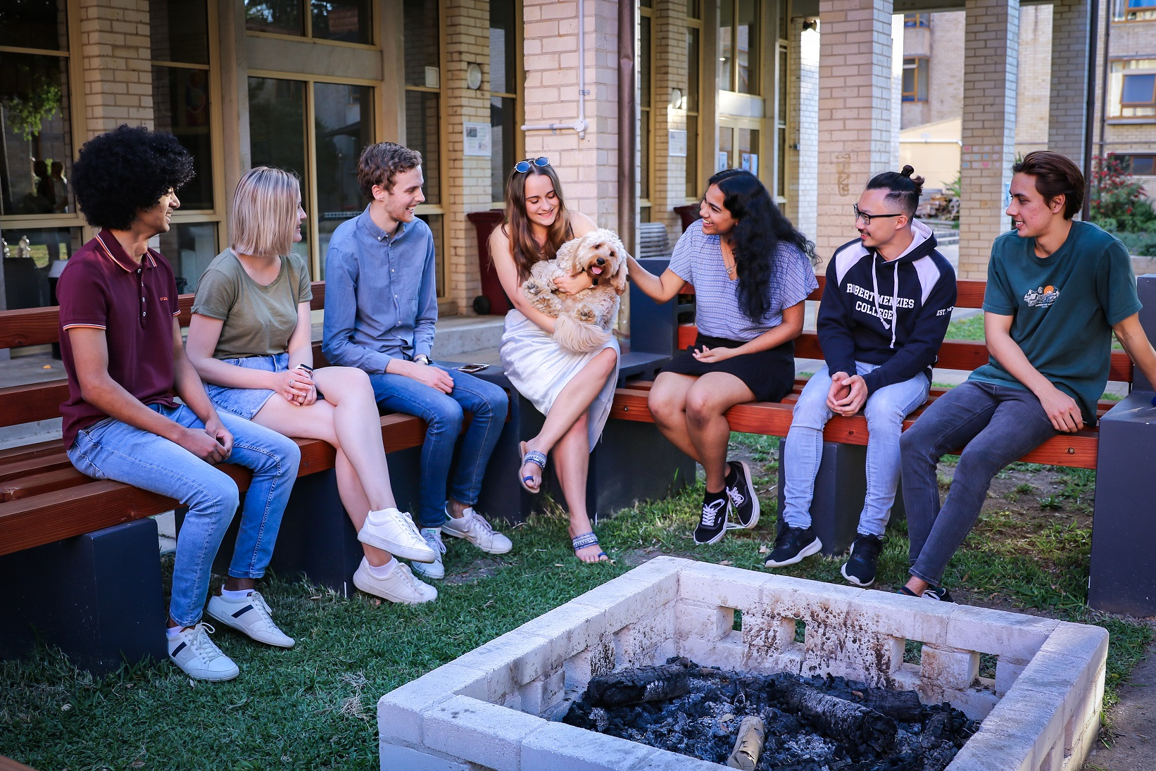 A group of Robert Menzies College university student residents sitting around a fire pit with a dog